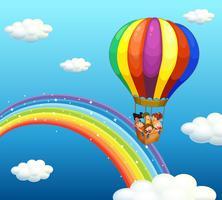 Enfants chevauchant dans un grand ballon au-dessus de l'arc-en-ciel