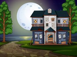 Spökat hus vid sjön på natten