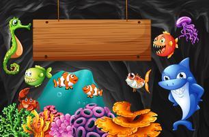 Animaux marins nageant autour d'un panneau en bois