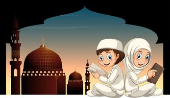 Two muslim kids reading book with mosque background