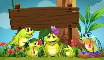 Wooden sign with frogs in field