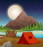Camping con tienda de campaña junto al río por la noche.