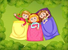 Tre tjejer sover på grönt gräs