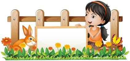 A girl holding a white board with a rabbit inside the wooden fence