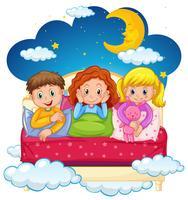 Tres niños en pijama por la noche.