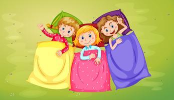 Tre ragazze che dormono sull'erba verde