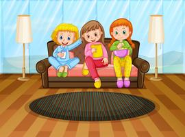 Tre tjejer äter mellanmål i vardagsrummet