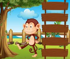 Un mono al lado de un cartel de madera.