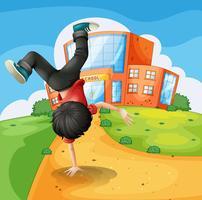 Ein Junge macht Breakdance entlang der Schule