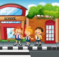 Tres estudiantes esperando para cruzar la calle.