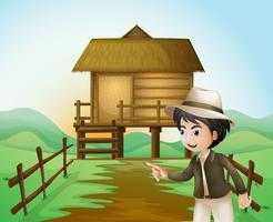 A boy with a hat standing near the nipa hut