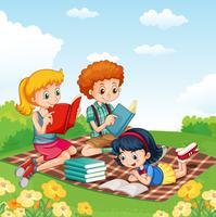 Bambini che leggono libri nel parco