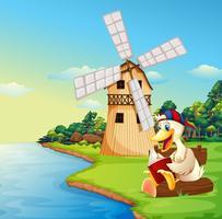 Un pato leyendo un libro cerca del molino de viento.