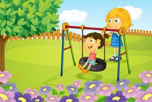 Barnen spelar gunga i trädgården