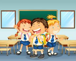 Tre bambini sorridenti all'interno dell'aula