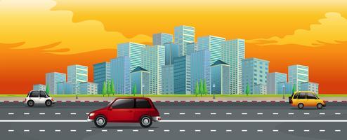 Vista de la carretera con la ciudad moderna y el cielo dorado