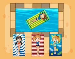 Eine Gruppe von Mädchen bräunt sich neben dem Pool