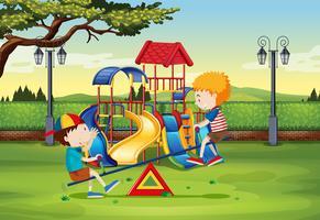 Chicos jugando en balancín en el parque