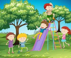 Niños jugando tobogán en el parque