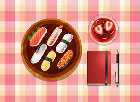 A table with sushi, a cocktail drink, a ballpen and a notebook