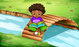 Ein Junge liest an der Brücke
