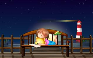 Little girl reading on the bench at night