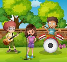 Three children playing music in park