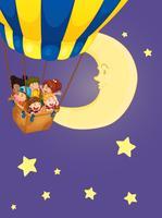 Niños montados en globo por la noche.