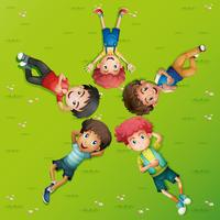 Five boys lying on green grass
