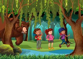 Urso pardo em pé atrás dos caminhantes na floresta