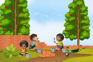 Tre barn lägger tegelstenar i trädgården