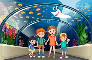 Crianças que visitam o aquário cheio de peixe
