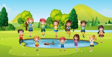 Jungen und Mädchen stehen um den Teich herum