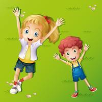 Två barn ligger på gräset
