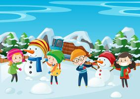 Niños haciendo muñeco de nieve en el campo.