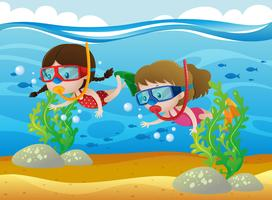 Two girls diving under the sea