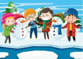 Niños felices con muñeco de nieve en invierno