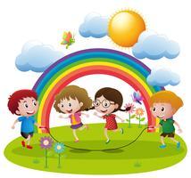Cuatro niños saltando la cuerda en el jardín