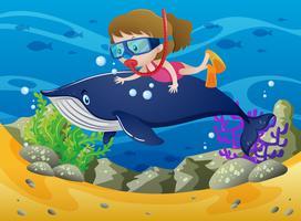 Chica buceando con ballena bajo el mar.