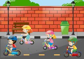 Quattro bambini in sella alla bici sulla strada