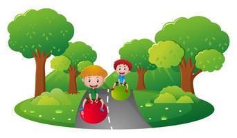 Deux garçons jouant sur une grosse balle sur la route