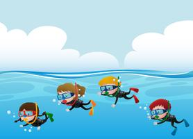 Four kids scuba diving under the ocean