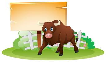 Letrero de madera y toro marrón.