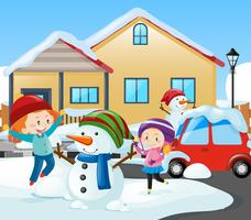 Zwei Mädchen und Schneemann vor dem Haus