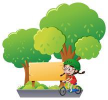 Sinal de madeira e menina andando de bicicleta no parque