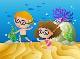 Dos niños buceando bajo el mar.