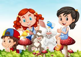 Tres niñas y conejos en el jardín.