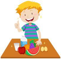 Kleiner Junge und gesundes Lebensmittel auf Tabelle