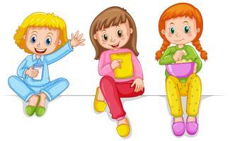 Drei Mädchen in den Pyjamas Snacks essen
