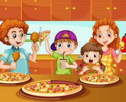 Familj med pizza i köket